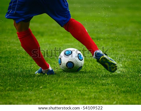 football player kicks the ball, free kick - stock photo