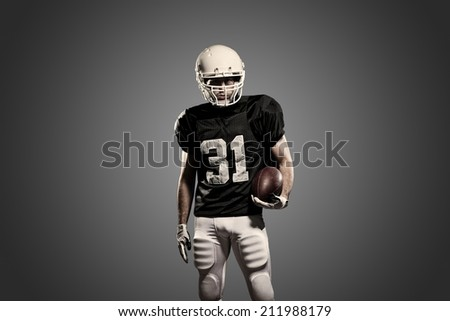 Football Player on a black uniform, on a black background.
