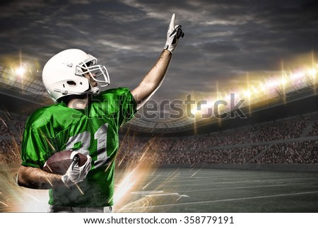 Football Player on a green uniform celebrating on a Stadium.