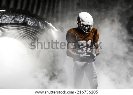 Football player, on a orange uniform, leaving a smoky tunnel, ready to get on the field.