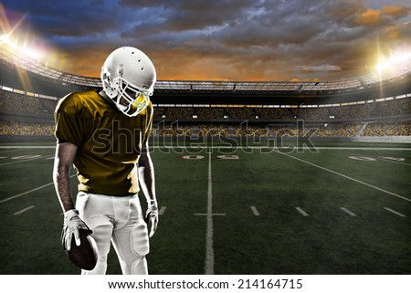 Football Player on a yellow uniform, on a stadium background.
