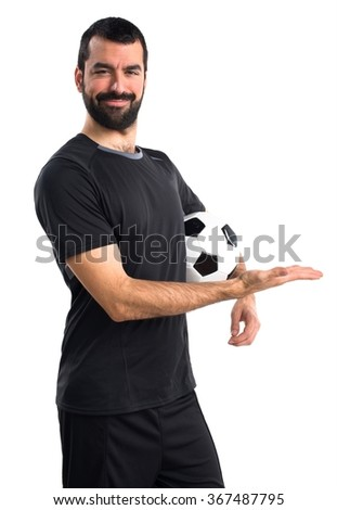 Football player presenting something - stock photo