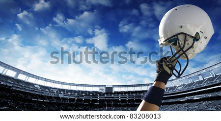 Football Player raises his helmet before an important game - stock photo