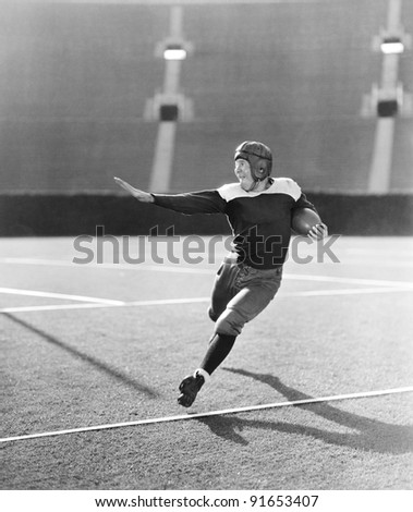 Football player running with ball - stock photo