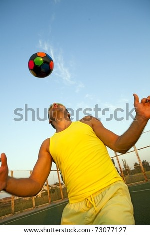 Football player shooting a ball with his head - stock photo