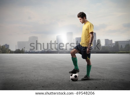 Football player standing on a field with cityscape on the background - stock photo