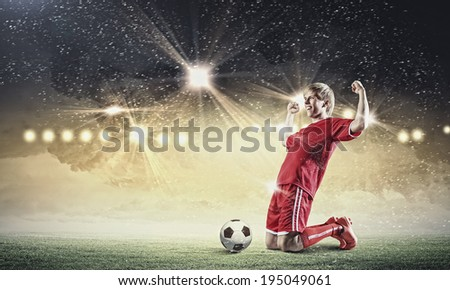 Football player standing on knees and screaming with joy