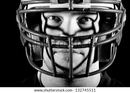 Football Player - This is a high contrast, black and white image of a young adult wearing a football helmet with an intense look on his face. - stock photo
