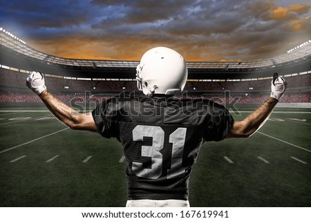 Football Player with a black uniform celebrating on a stadium.