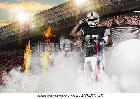 Football Player with a black uniform coming out of a stadium tunnel.
