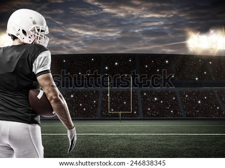 Football Player with a Black uniform on a stadium. - stock photo