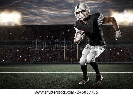Football Player with a Black uniform running on a stadium. - stock photo