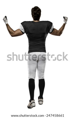 Football Player with a black uniform walking, showing his back on a white background. - stock photo