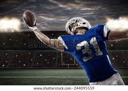 Football Player with a blue uniform catching a ball on a stadium.