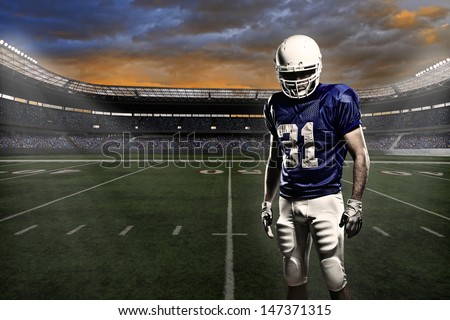 Football player with a blue uniform, in a stadium with fans wearing blue uniform - stock photo