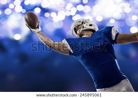 Football Player with a blue uniform making a catch on a blue lights background. - stock photo