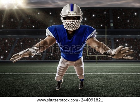 Football Player with a blue uniform making a tackle on a stadium. - stock photo
