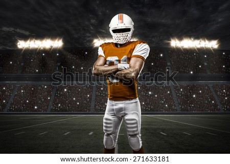 Football Player with a orange uniform on a stadium. - stock photo