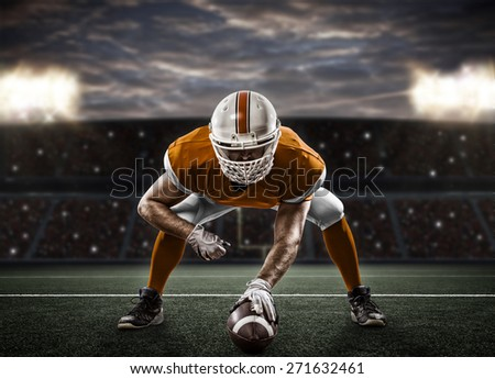 Football Player with a orange uniform on the scrimmage line, on a stadium. - stock photo