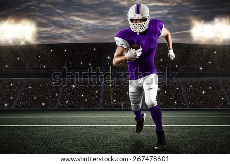 Football Player with a purple uniform running on a stadium. - stock photo
