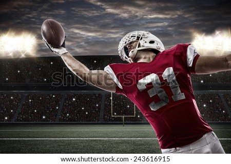 Football Player with a red uniform catching a ball on a stadium.. - stock photo