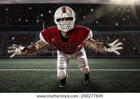 Football Player with a red uniform making a tackle on a stadium. - stock photo