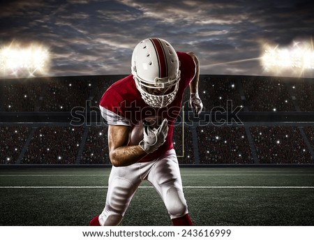 Football Player with a red uniform Running on a Stadium. - stock photo