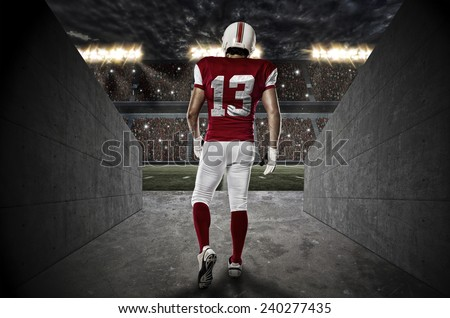 Football Player with a red uniform walking out of a Stadium tunnel. - stock photo