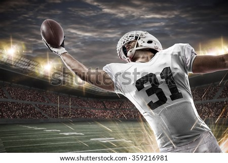 Football Player with a white uniform catching a ball on a stadium. - stock photo