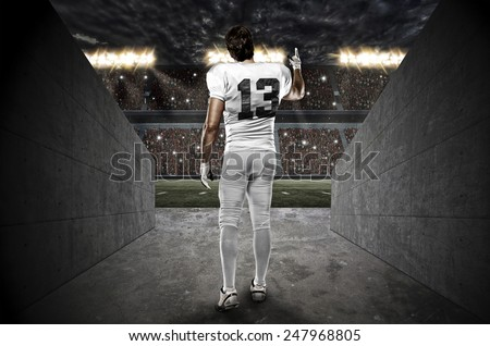 Football Player with a white uniform walking out of a Stadium tunnel. - stock photo