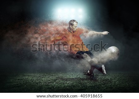 Football player with ball around splash drops on the stadium field - stock photo