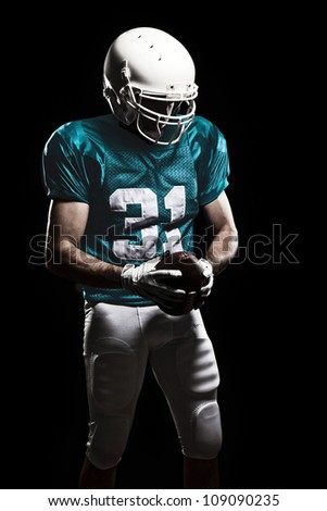 Football Player with number on the uniform, holding a ball. Studio Shot