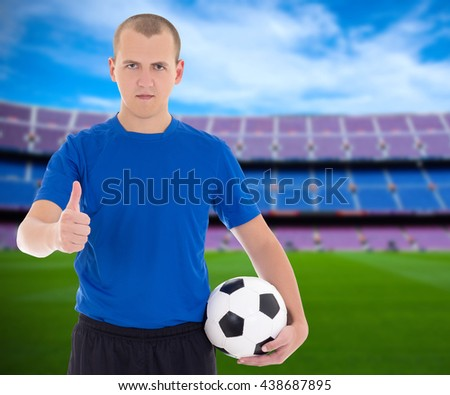 football player with soccer ball posing on field of big stadium
