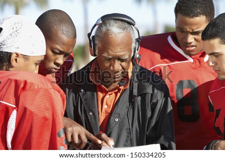Football players and coach discussing strategy together - stock photo