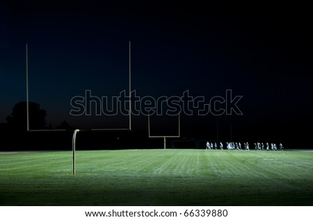 football players running on the field at night