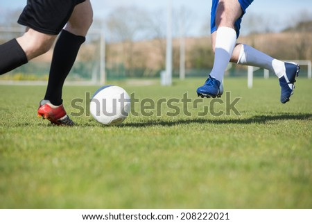 Football players tackling for the ball on pitch on a clear day - stock photo