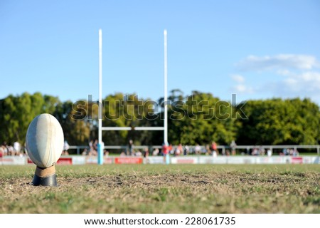 Football ready to be kicked between a set of goal posts on a sporting field. - stock photo
