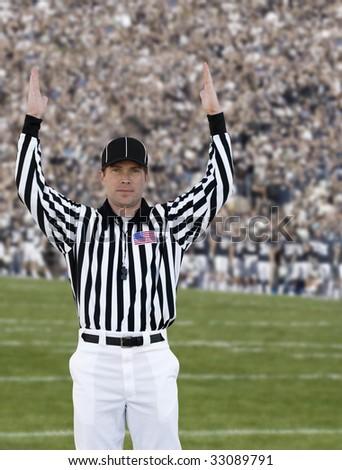 Football Referee signaling touchdown - stock photo