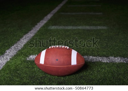 Football resting on a turf field at night. Lots of copy space with dramatic lighting - stock photo