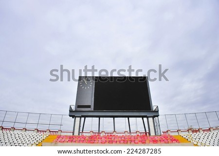 Football scoreboard with clock and empty tribune with overcast sky on background - stock photo