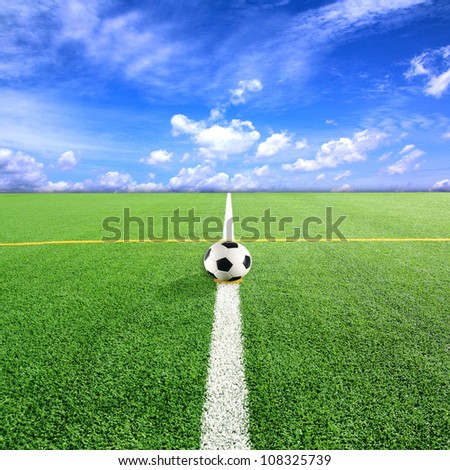 Football (Soccer) ball on grass field with blue sky  background - stock photo