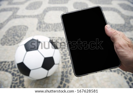 Football soccer ball with hands holding tablet in Rio de Janeiro Brazil - stock photo
