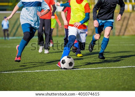 Football soccer game of youth teams. Running young players kicking soccer ball - stock photo
