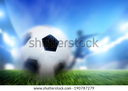 Football, soccer match. A player shooting on goal, ball in motion. Lights on the stadium at night. - stock photo