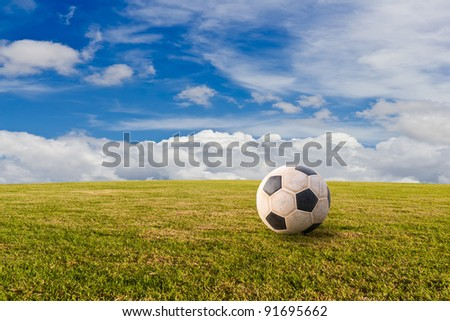 Football ( soccer ) on green lawn with blue sky - stock photo