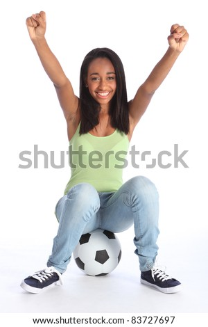 Football sports success for beautiful young African American teenage school girl soccer player, sitting on a ball with arms raised in triumph, with big happy smile. - stock photo