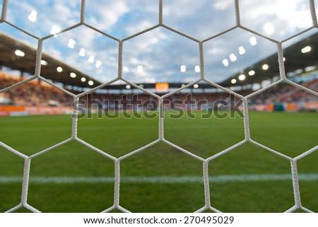 Football stadium - view by the net. - stock photo