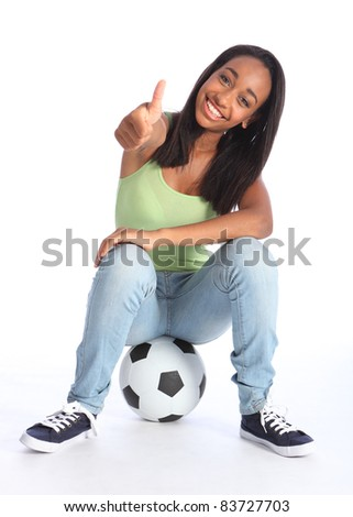 Football success for beautiful young African American teenage school girl soccer player, sitting on a ball with thumbs up sign. Girl wearing blue jeans and casual vest and has a big happy smile. - stock photo
