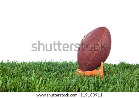 Football tee on green grass waiting for a kick off. White background for placement of copy. - stock photo