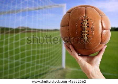 Football vintage ball in hand net soccer goal green grass background [Photo Illustration] - stock photo